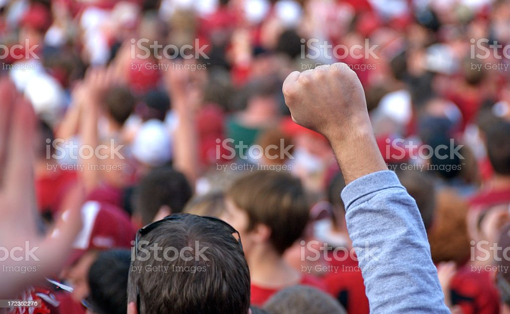 A crowd of people raising their fist royalty-free stock photo