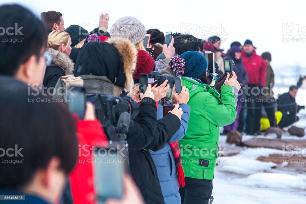 A crowd of people waiting for Strokkur geyser eruption stock photo
