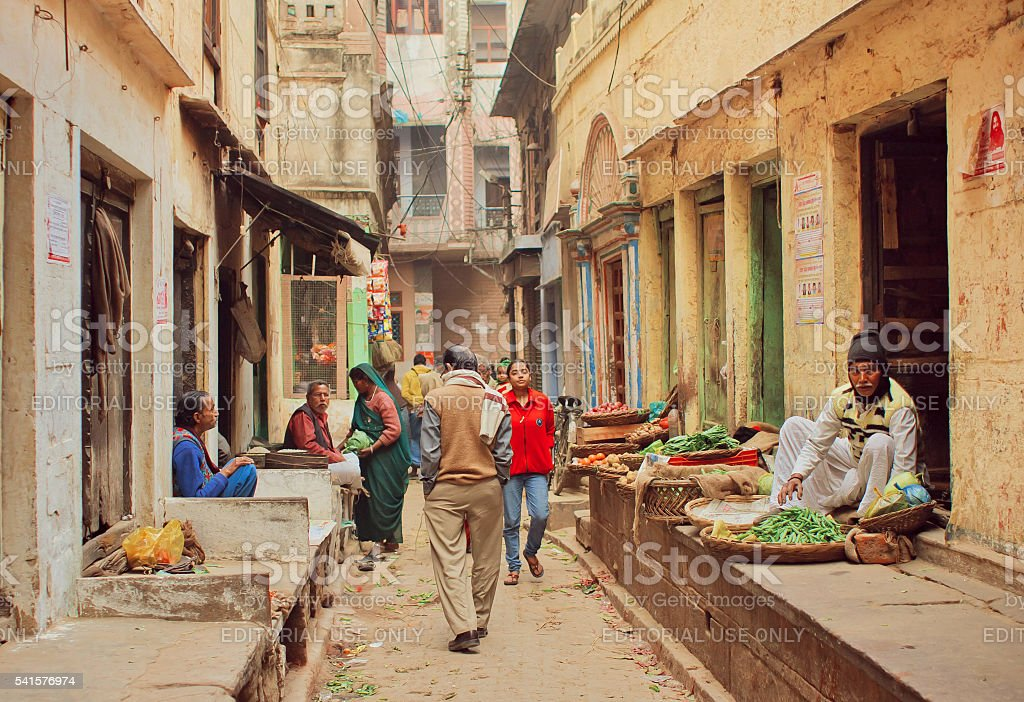 Crowd of people walking on narrow street with food sellers stock photo
