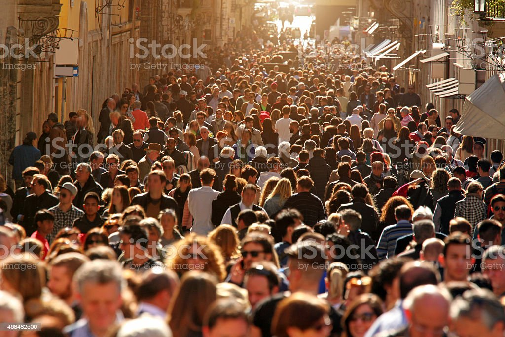 Crowd of people walking on street in downtown Rome, sunlight stock photo
