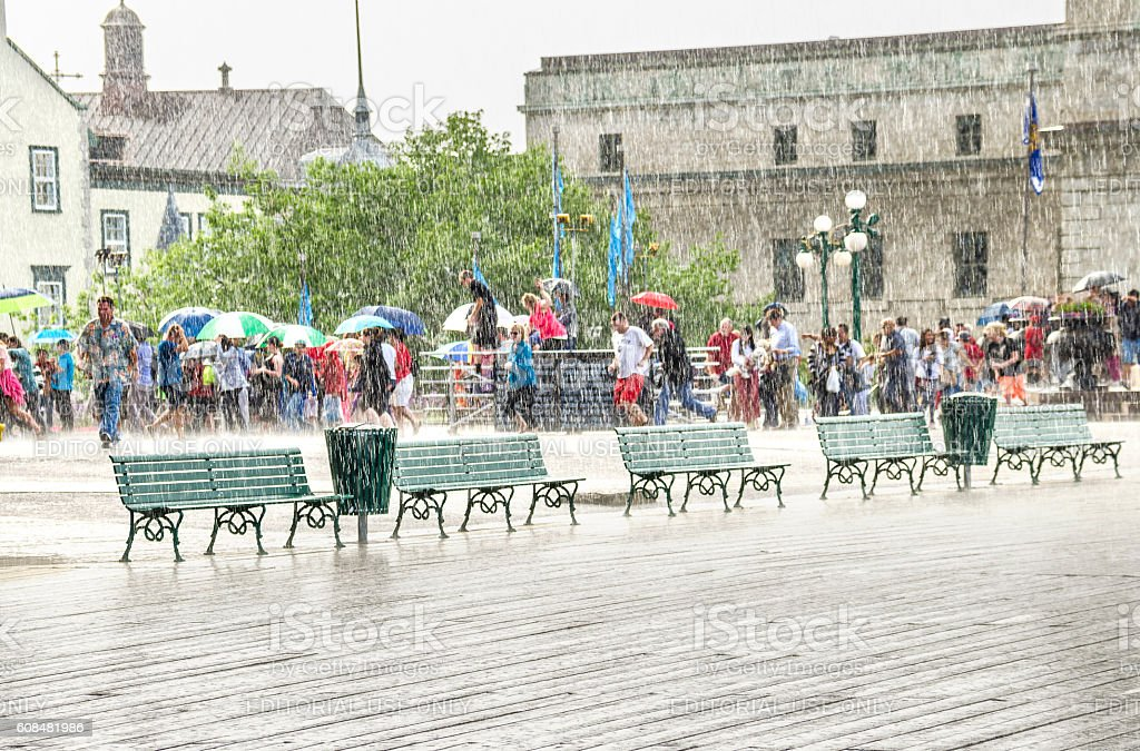 Crowd of people with umbrellas walking in heavy rain stock photo