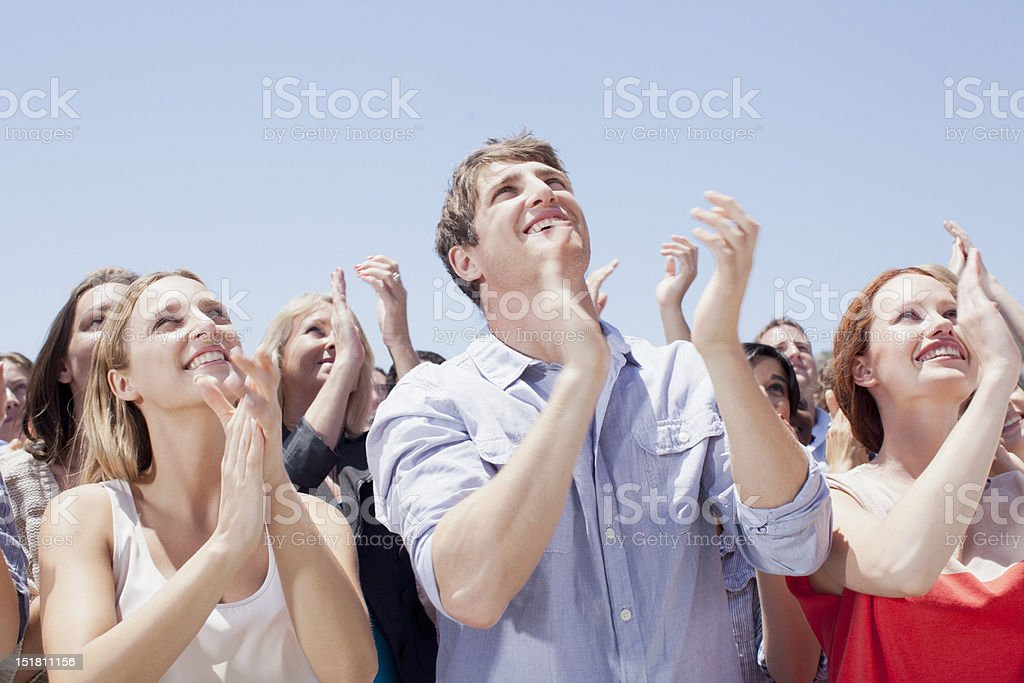 Crowd of smiling people clapping and looking up stock photo