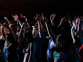 Crowd raising arms at party in night club