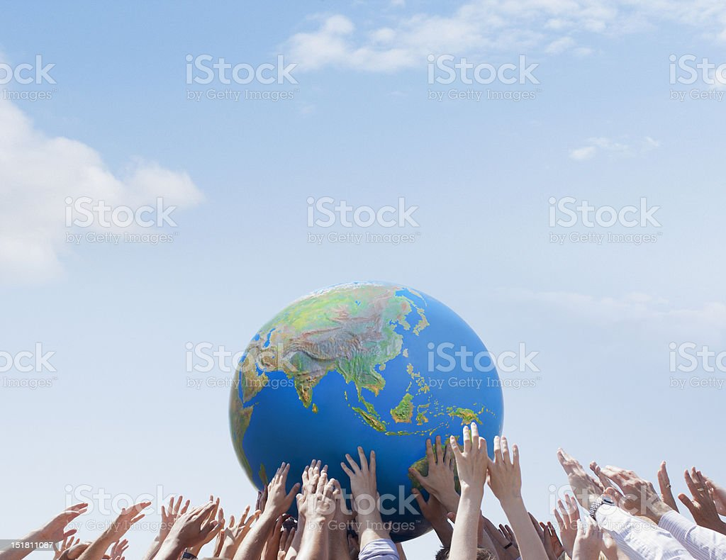 Crowd reaching for globe stock photo