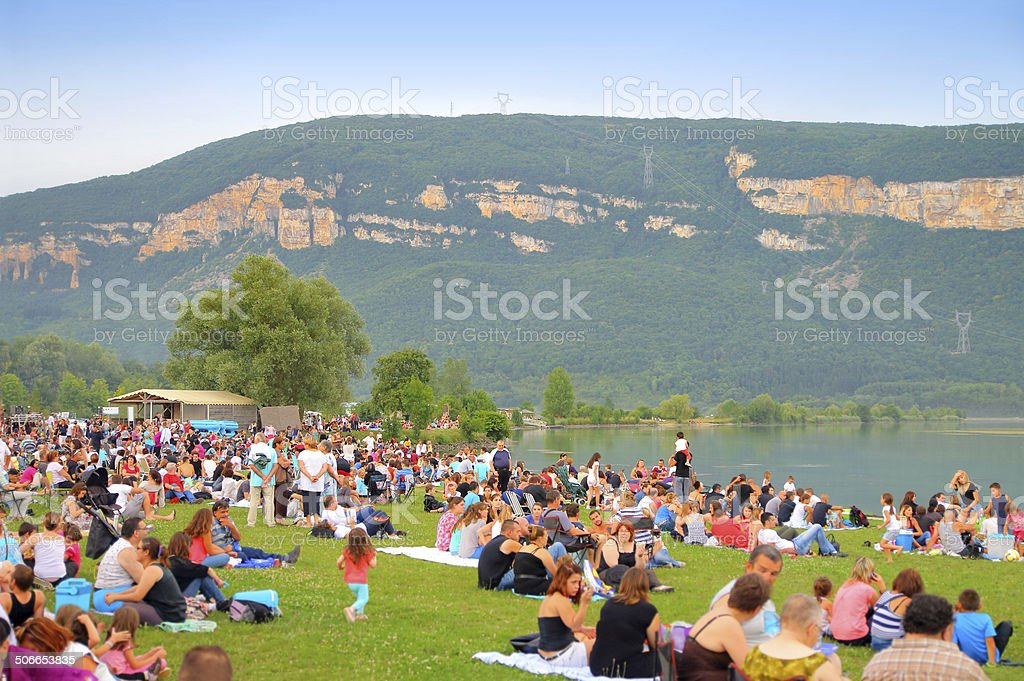 Crowd sitting in grass stock photo