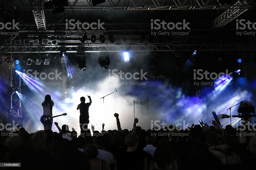Crowd view of concert with purple lights and fog stock photo