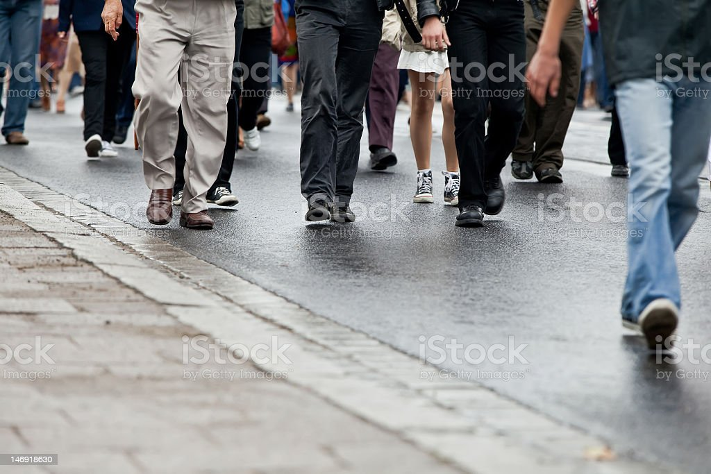 A photograph taken of a group of people walking, viewed from the...