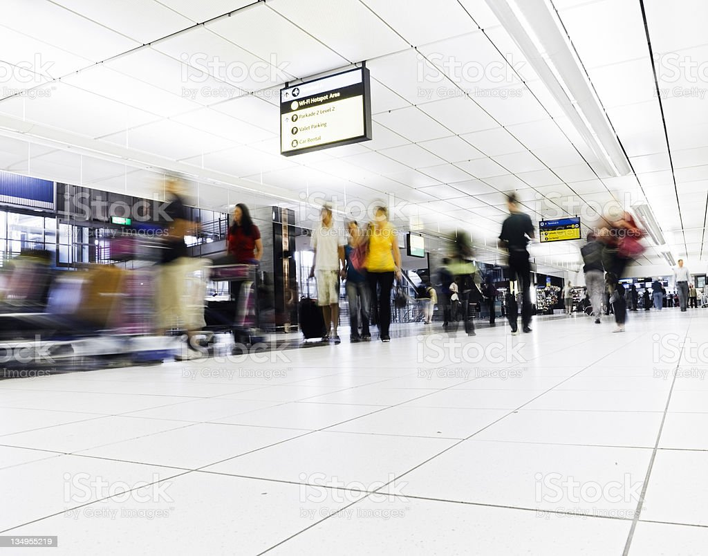 Crowd walks towards camera in an airport concourse royalty-free stock photo