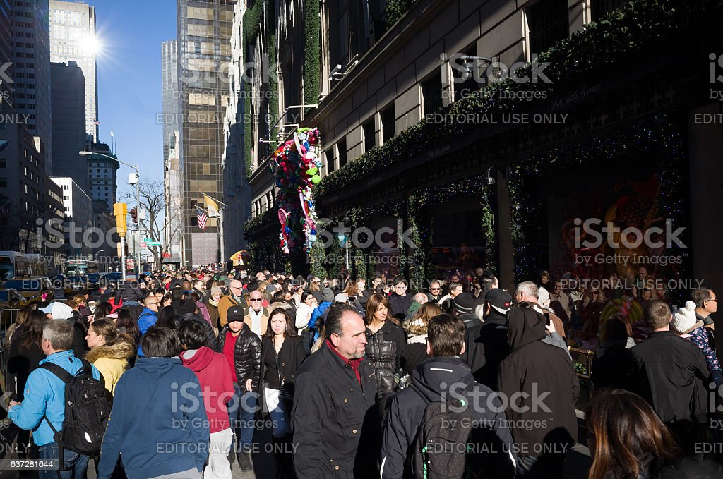 Crowded sidewalk in front of Saks Fifth Avenue windows displays stock photo
