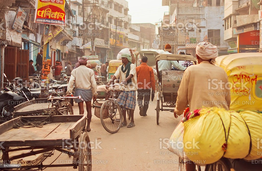Crowded street with cargo workers and cyclists stock photo