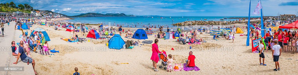 Crowds of tourists enjoying ocean beach Lyme Regis Dorset UK stock photo