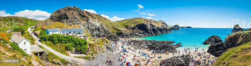 Crowds of tourists on summer holiday beach Kynance Cove Cornwall stock photo