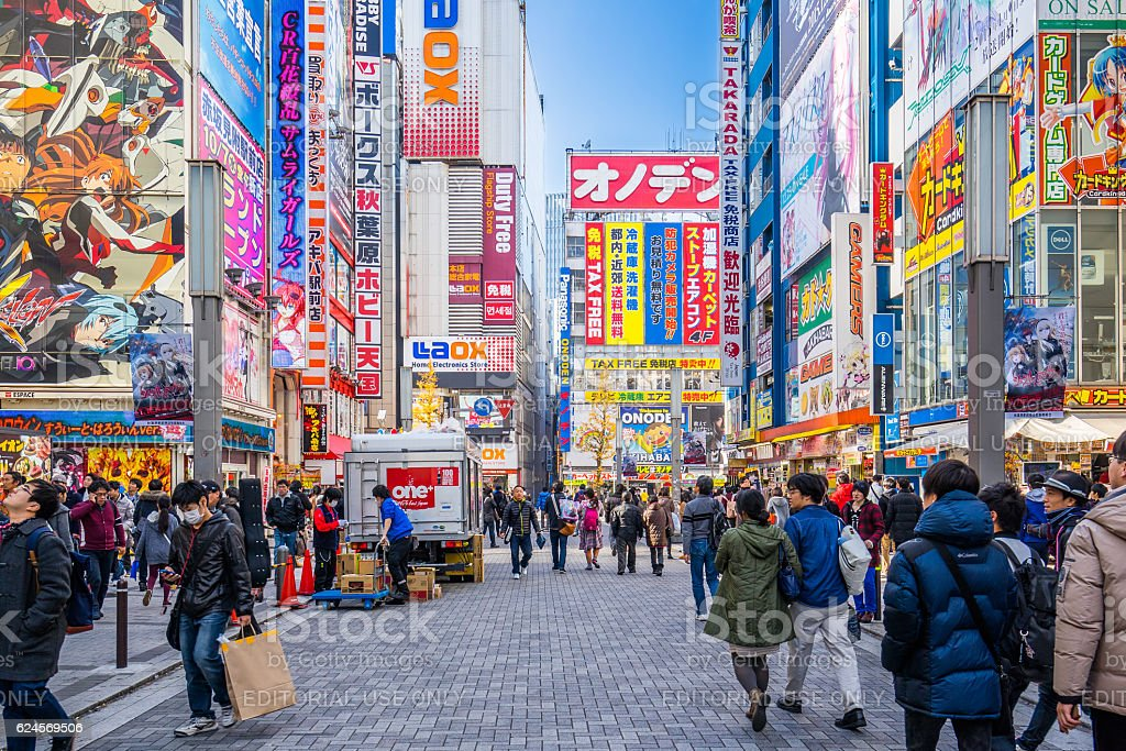 Crowds pass below colorful signs in Akihabara the electronic district stock photo