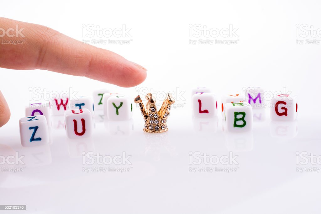 Crown between Letter cubes stock photo