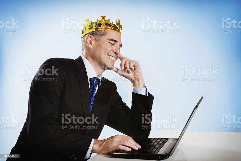 Crowned businessman smiles down at his laptop royalty-free stock photo