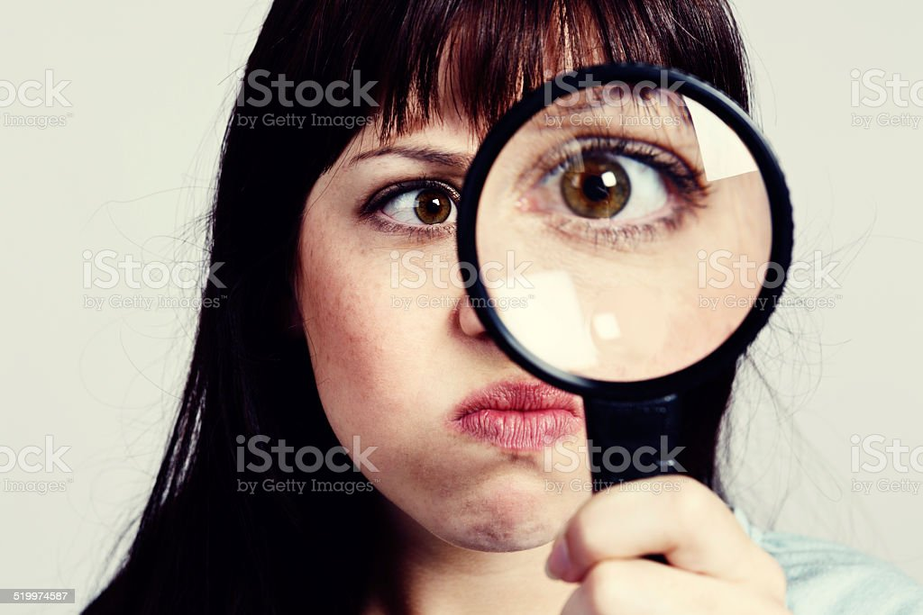 Crowsfeet? Pimple? Cute, pouting woman examines eye with magnifying glass stock photo