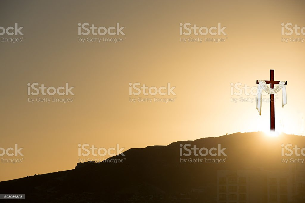 Crucifix at sunrise on Easter morning with  shroud.- copy sapce stock photo