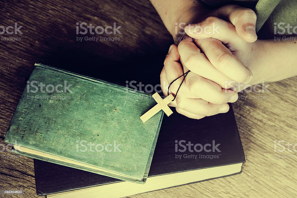 Crucifix in hand on the Holy Bible. stock photo