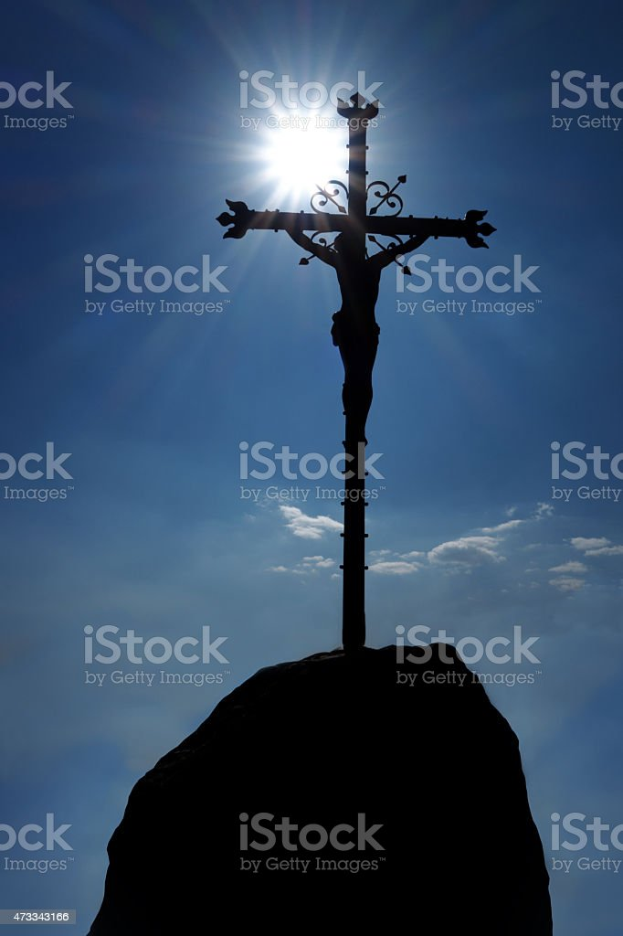Crucifx on a rock in the backlight stock photo