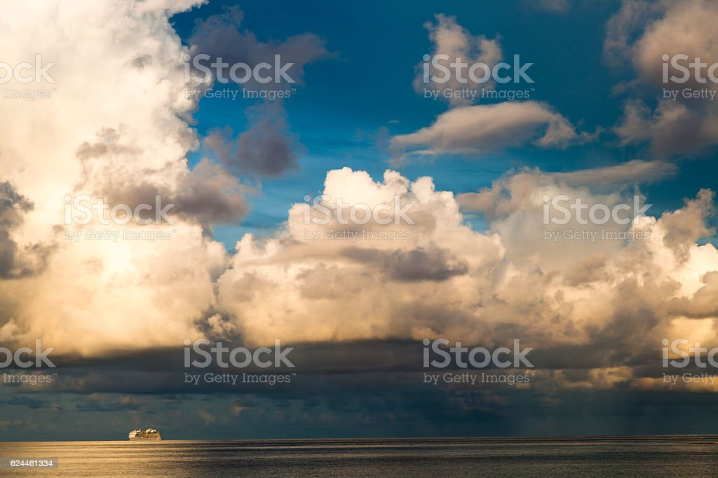 Cruise ship and darmatic day break clouds over the sea stock photo
