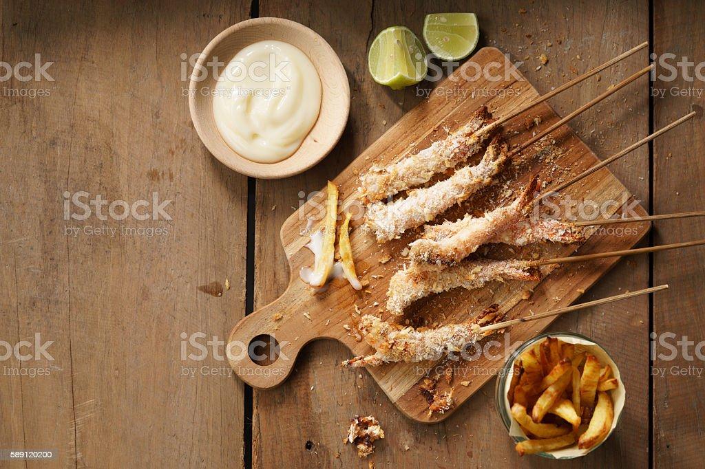 crumbed prawn skewers with potato fries stock photo