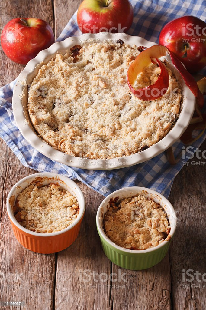 Crumble with apples close-up in baking dish. Vertical stock photo