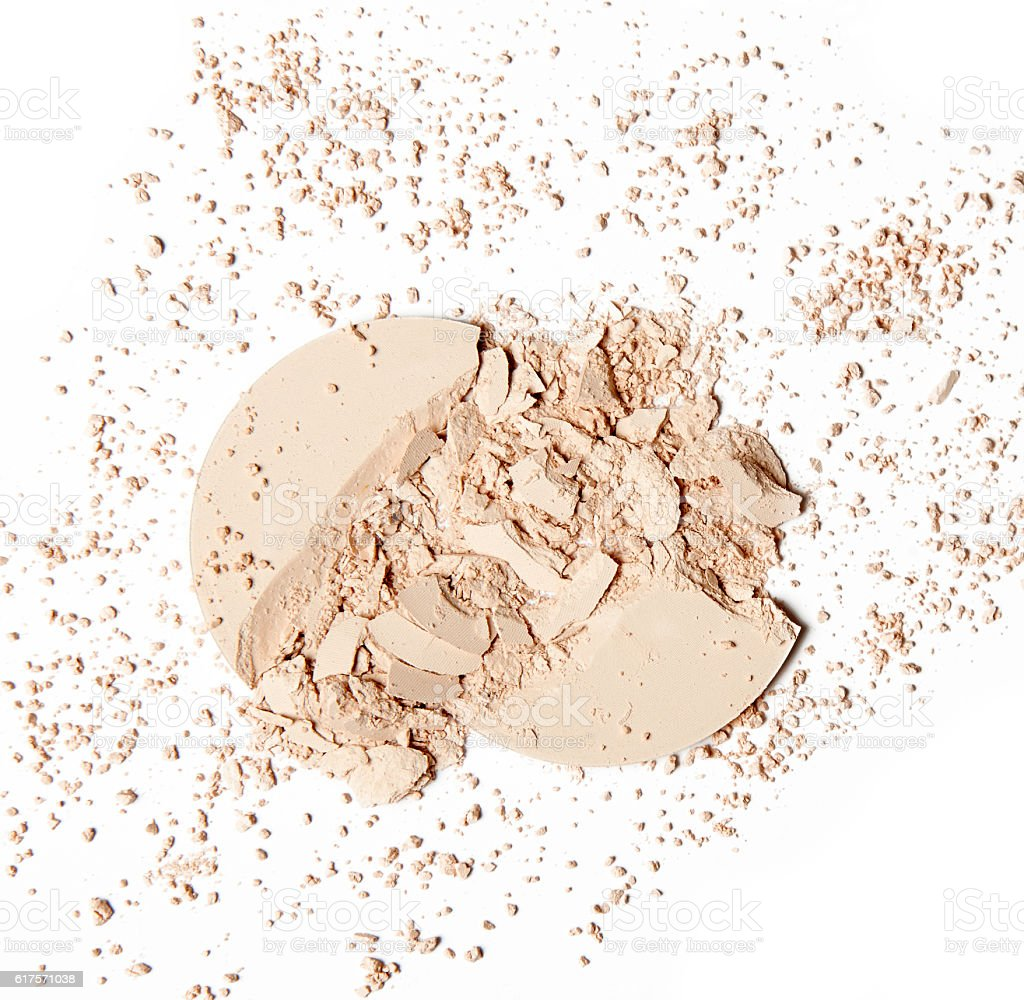crumbled beige powder on white background stock photo