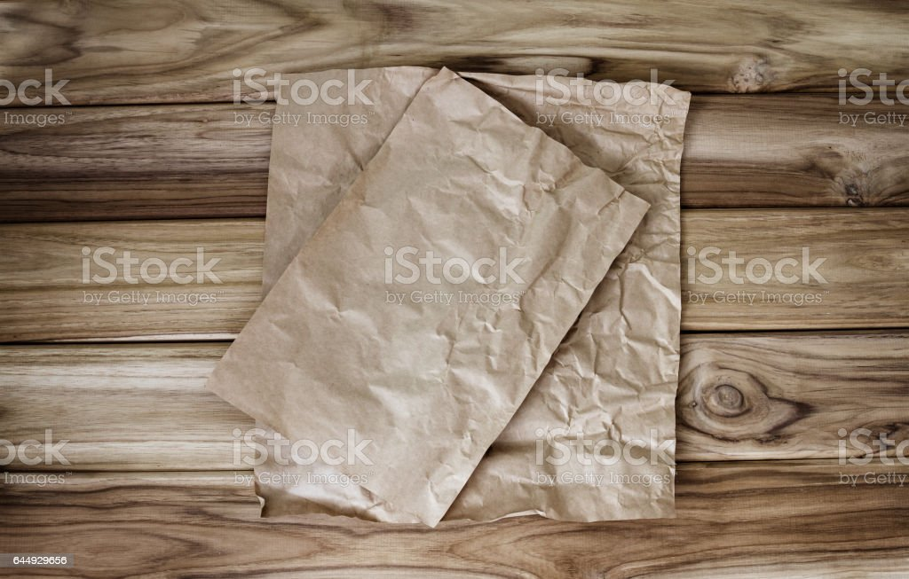 Crumbled cooking or baking paper sheet place on wooden table stock photo