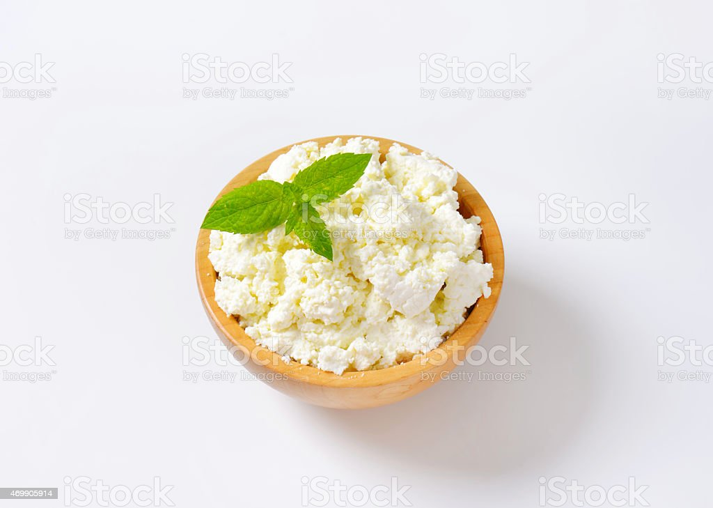 Crumbly cheese in wooden bowl, isolated on white background stock photo