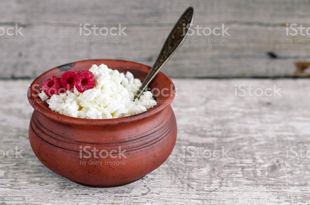 Crumbly homemade cottage cheese in a clay pot stock photo