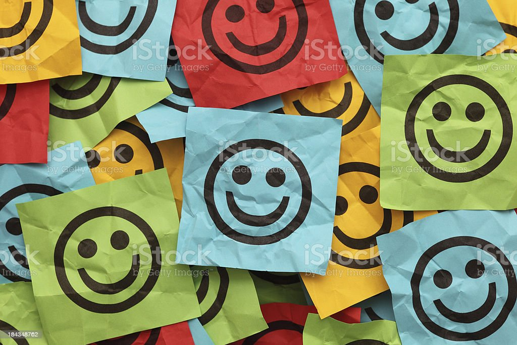 Crumpled adhesive notes with smiling faces royalty-free stock photo
