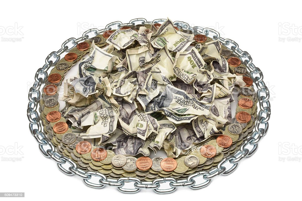 crumpled dollar surrounded by coins stock photo