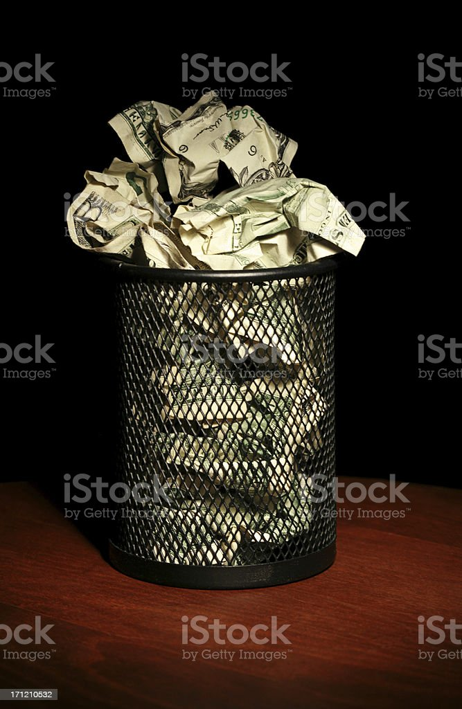 Crumpled money in a black waste basket stock photo