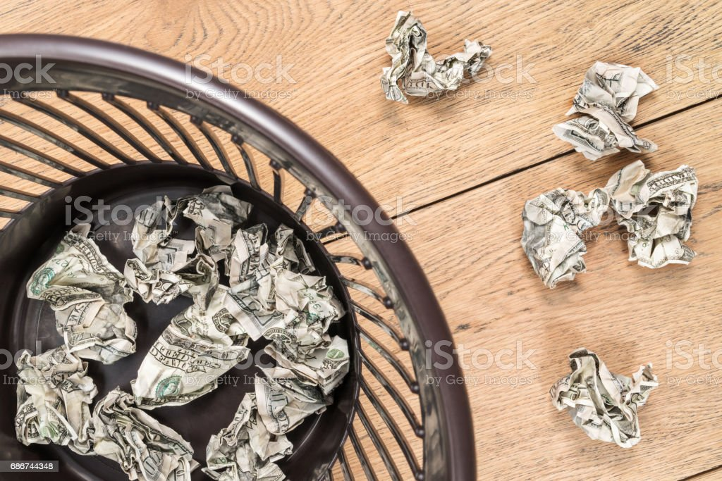 Crumpled money in trash stock photo