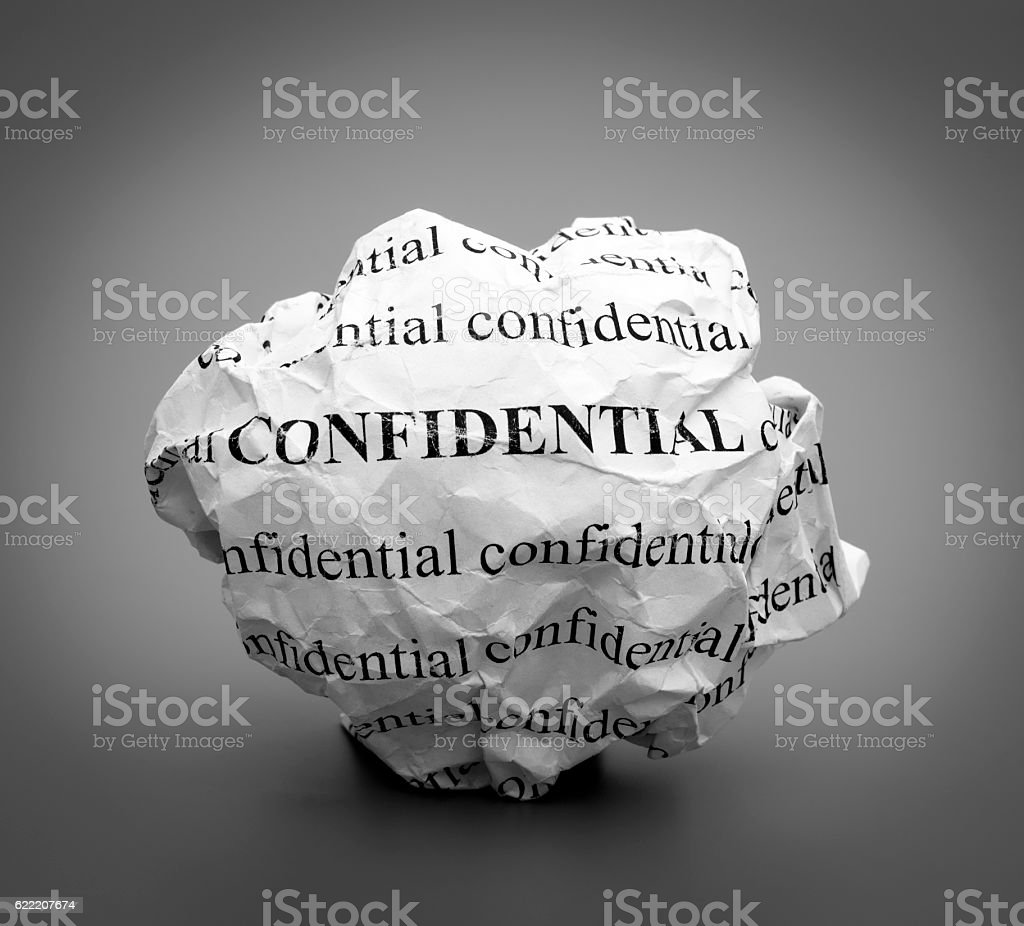 Crumpled paper ball with words Confidential on gray background stock photo