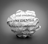 Crumpled paper ball with words Confidential on gray background