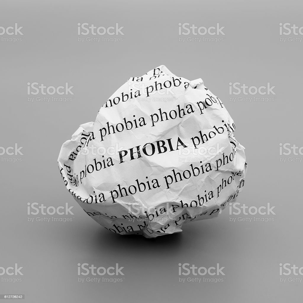 Crumpled paper ball with words Phobia on gray background stock photo