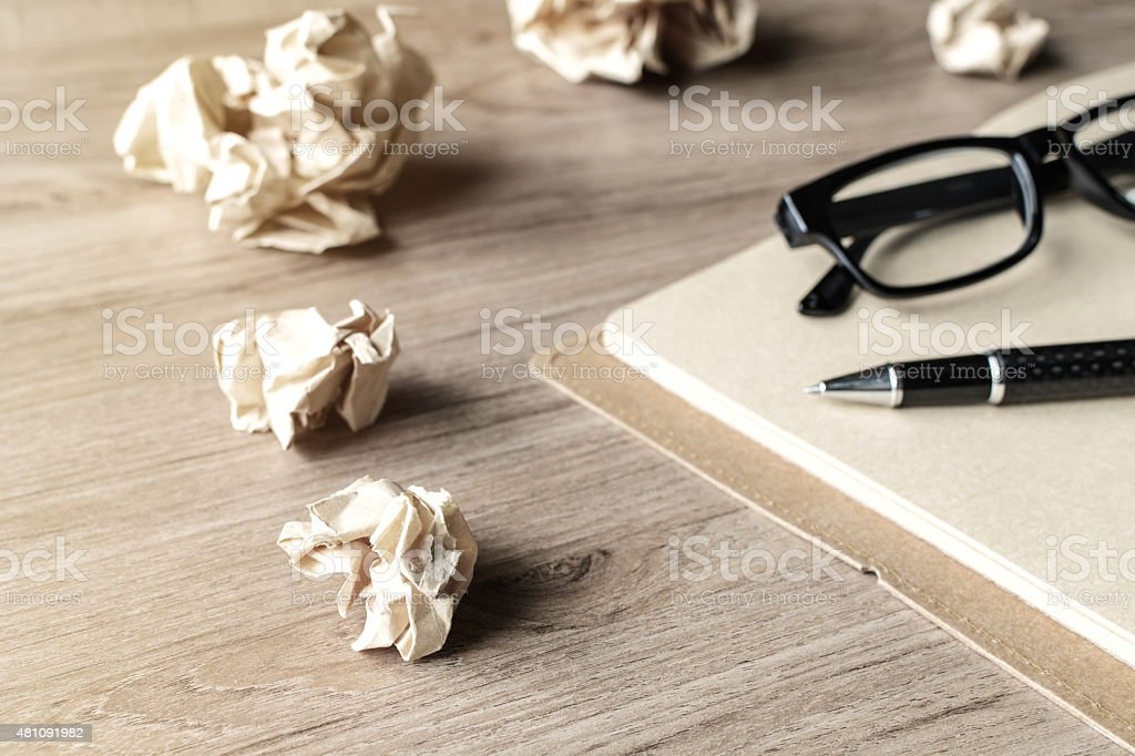 Crumpled paper balls with eye glasses and notebook stock photo