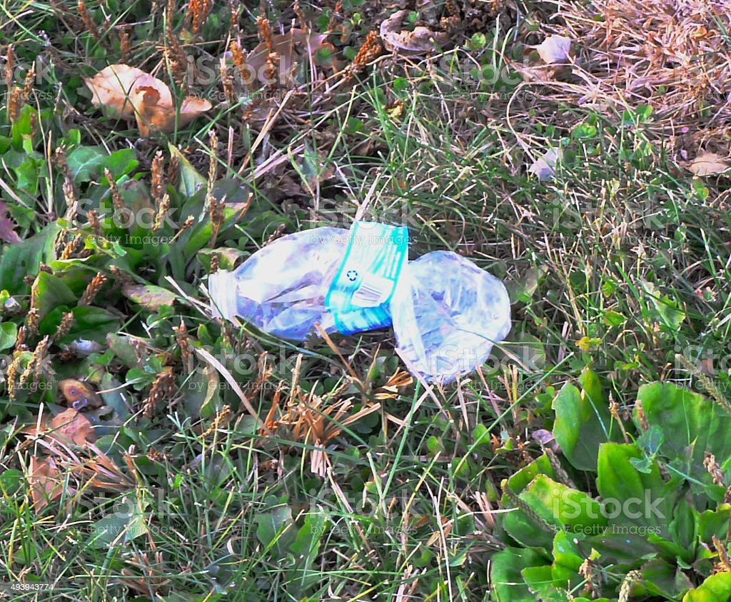 Crumpled plastic bottle lying on the ground stock photo
