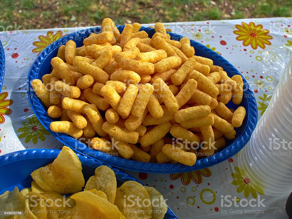 Crunchy cheese snacks puffs doodles in a blue bowl stock photo
