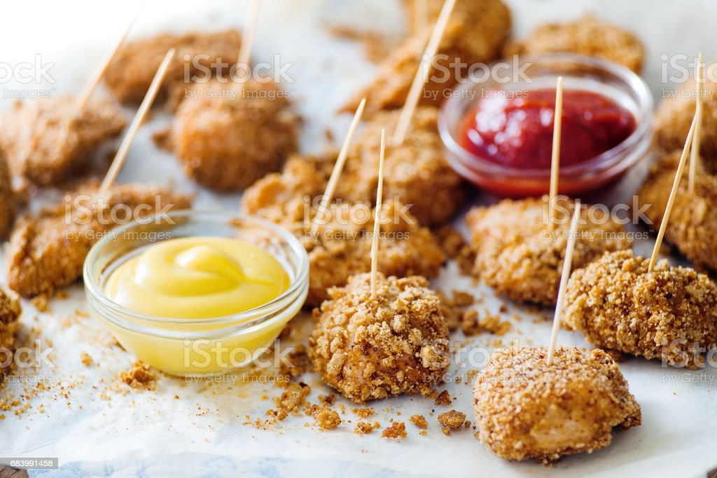 Crunchy nuggets on skewers with two sauces stock photo