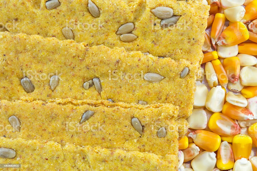 Crunchy oat thins with sunflower surrounded by dried corn grains stock photo