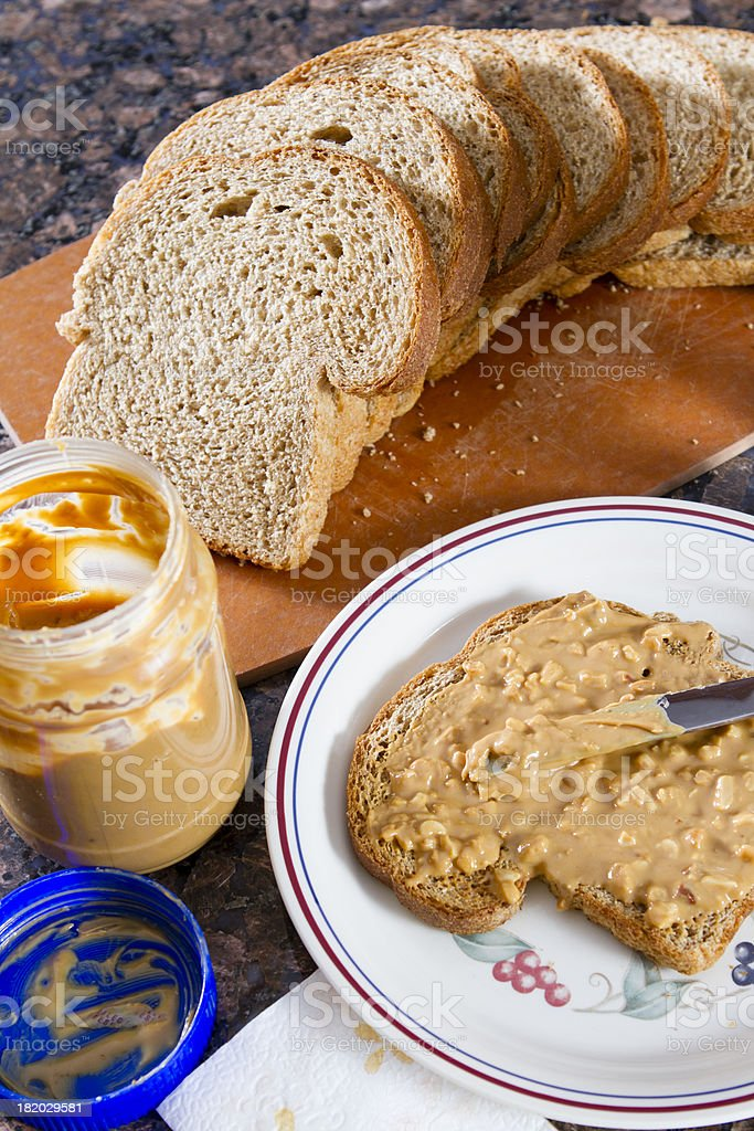 Crunchy peanut butter spread on a piece of bread. stock photo