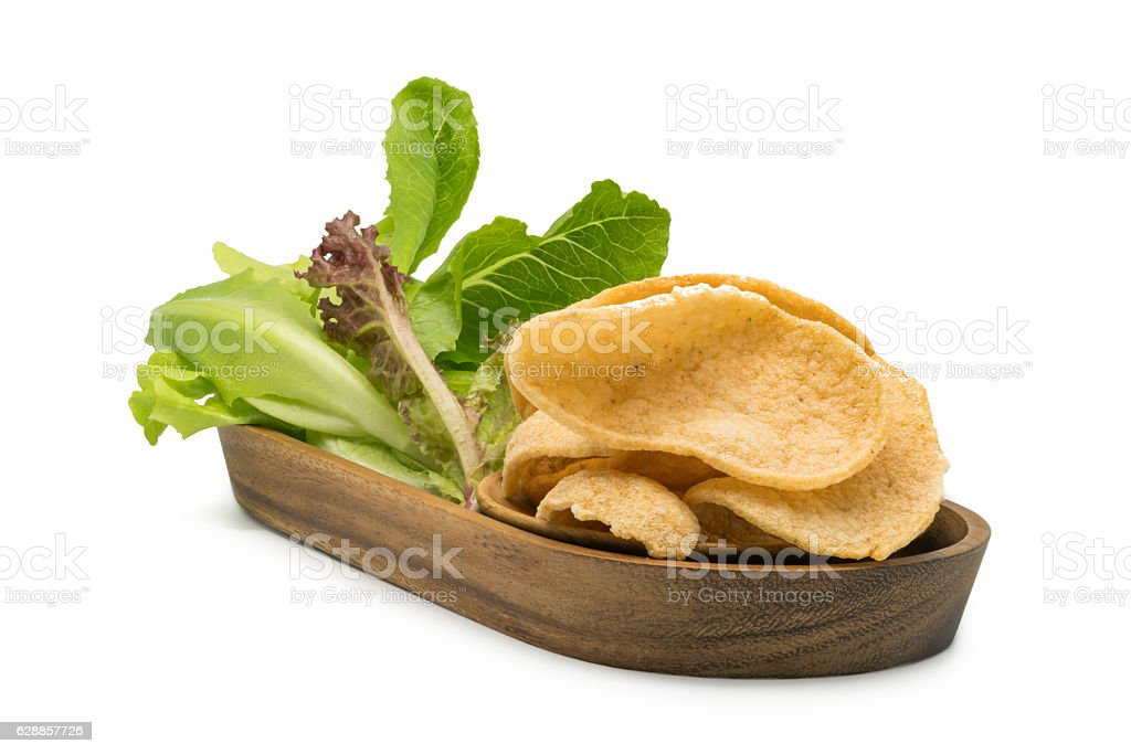 Crunchy prawn cracker and vegetables in a wooden tray stock photo