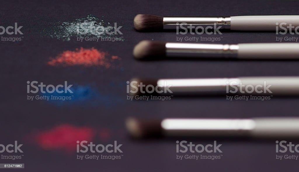 Crushed eye shadow and brush  isolated on black stock photo