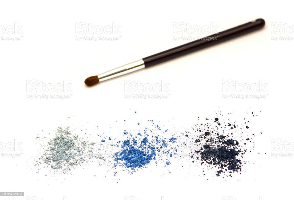 Crushed eye shadow and brush  isolated on white stock photo