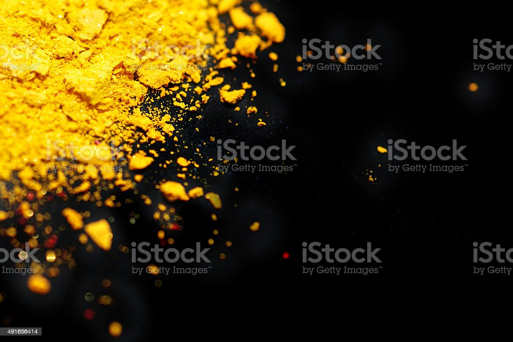 Crushed eyeshadow yellow color, Black background stock photo