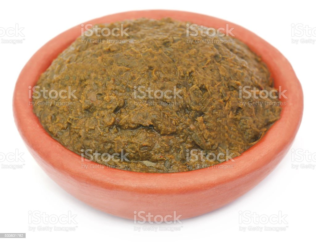 Crushed henna leaves in a pottery stock photo