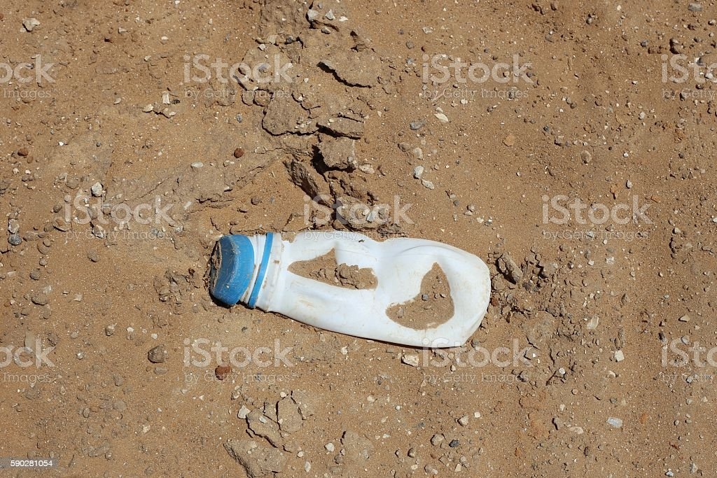 Crushed Plastic Bottle of Milk Product on the Ground. stock photo