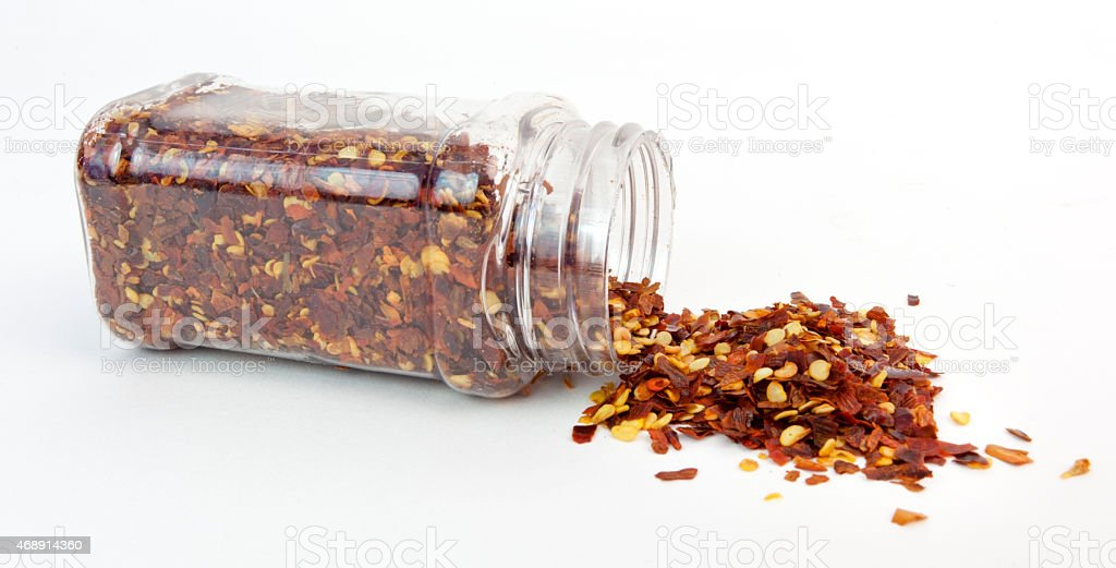 Crushed Red Pepper Spilling from Jar stock photo